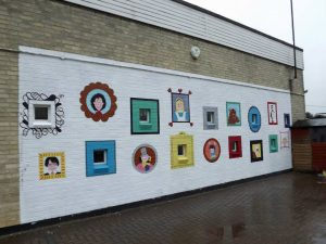 Art gallery mural featuring book characters in a school playground